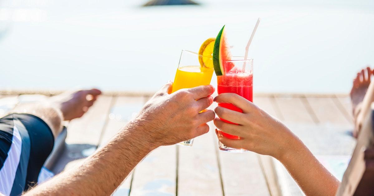 ビーチサイドで乾杯するカップルの手